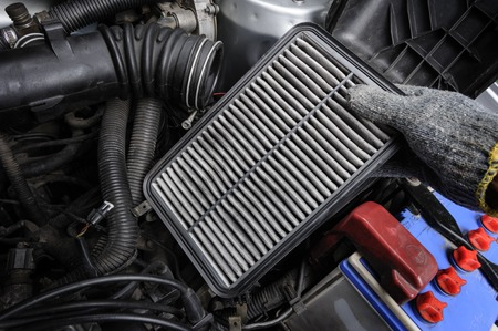 technician changing the air filter for car