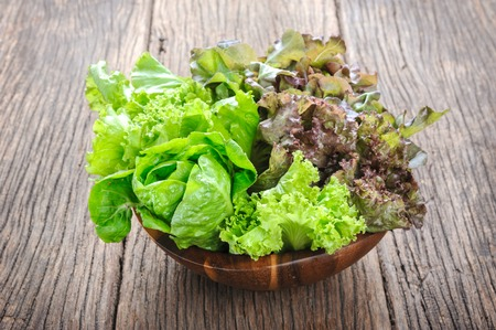 lechuga: primer aislar lechugas frescas en cuenco de madera sobre la mesa de madera