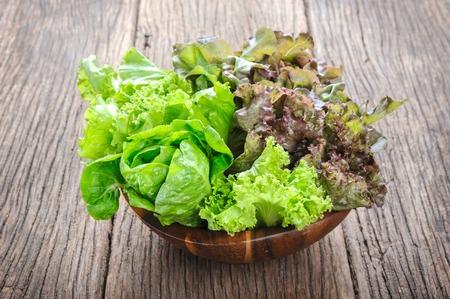 closeup isolate fresh lettuces in wooden bowl on wooden desk Archivio Fotografico