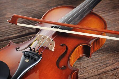 violin background: closeup new classical violin on wooden background Stock Photo
