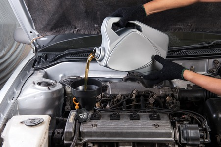 technician pouring fresh motor oil to engine of old car