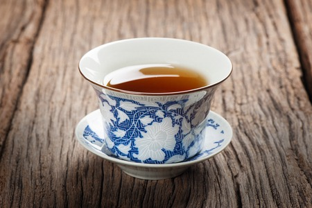 tea cup with tea leaf isolated on wooden plank