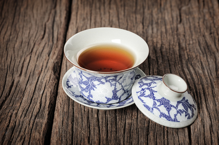 chinese teapot: tea cup with tea leaf isolated on wooden plank