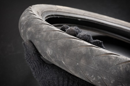 swerve: closeup old motorcycle rubber tires in technician hand Stock Photo
