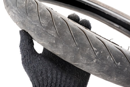 closeup old motorcycle rubber tires in technician hand Stock Photo