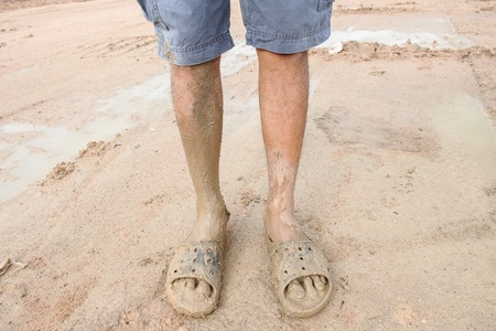 wearing sandals: man wearing dirty sandals after mired in the mud