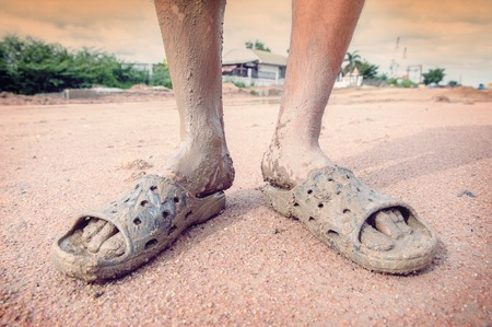 wearing sandals: man wearing dirty sandals after mired in the mud with filtered Stock Photo