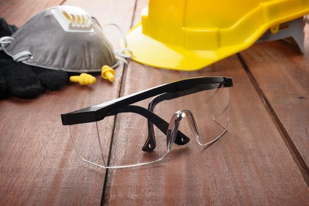 work safety: safety glasses on wooden plank