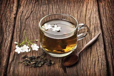 chinese herbs: a cup of tea on wooden plank Stock Photo