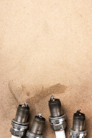 soot: used spark plugs with soot on wooden background Stock Photo