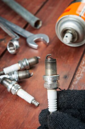 soot: used spark plug with soot in technician hand
