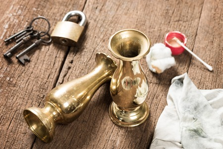 polishing: cleaning and polishing old brass jar Stock Photo