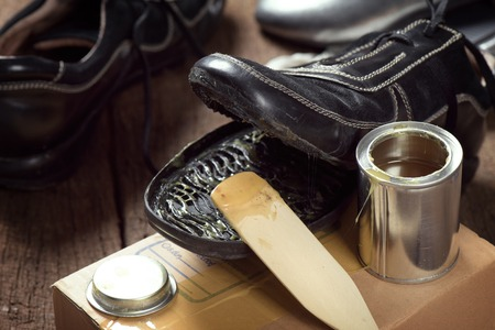 with shoe: applying rubber adhesive to the shoe, shoe repair Stock Photo
