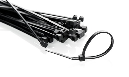 electrical materials: heap of black cable ties on white background Stock Photo