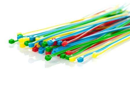 electrical materials: heap of colorful cable ties on white background