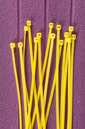 electrical materials: heap of yellow cable ties on purple background Stock Photo
