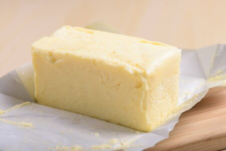 unwrapped: closeup creamy butter in its unwrapped foil paper Stock Photo