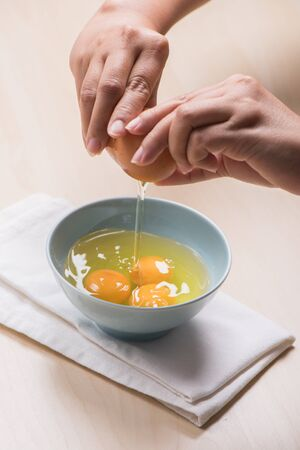 cracking: cracking eggs in to the bowl