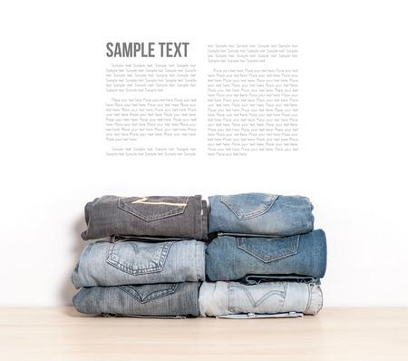 mezclilla: pila de jeans aislar en el escritorio de madera
