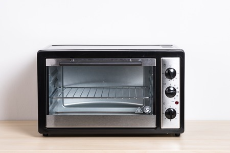 oven tray: small electric oven isolated in the kitchen Stock Photo