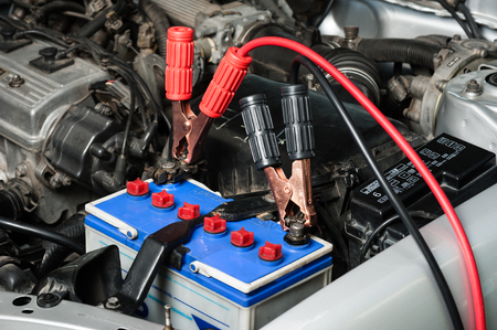 car battery with jumper cable in engine room Standard-Bild
