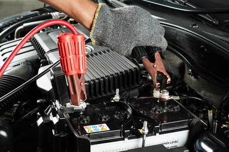 engine room: car battery with jumper cable in engine room Stock Photo