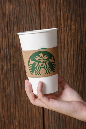 17 20: BANGKOK, THAILAND - MARCH 17, 2015: White paper cup with Starbucks logo in hand. Starbucks is the worlds largest coffee house with over 20,000 stores in 61 countries.