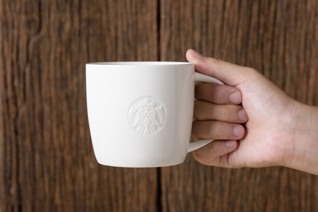 17 20: BANGKOK, THAILAND - MARCH 17, 2015: White cup with Starbucks logo in hand. Starbucks is the worlds largest coffee house with over 20,000 stores in 61 countries. Editorial