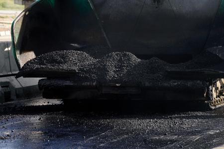paver: closeup hot asphalt in the hopper of asphalt paver machine Stock Photo
