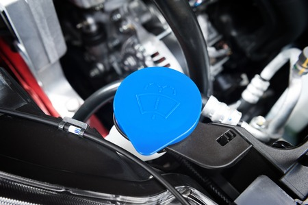 fluid: closeup blue windshield washer fluid reservoir cap in engine room Stock Photo
