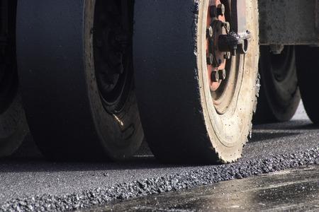closeup wheel of roller compactor at asphalt road construction site