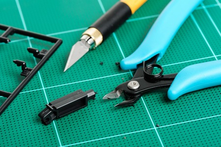 nippers: closeup blue plastic nippers on cutting mat Stock Photo
