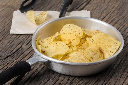 nosh: closeup potato chips in pan on wooden desk Stock Photo