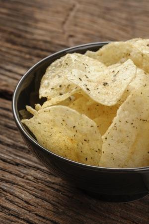 nosh: closeup potato chips in bowl on wooden desk