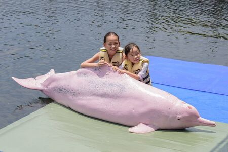 pink dolphin: CHANTHABURI, THAILAND - MAY 07, 2015: Unidentified two girls posing with Dolphin at Oasis Sea World in Chanthaburi, Thailand.