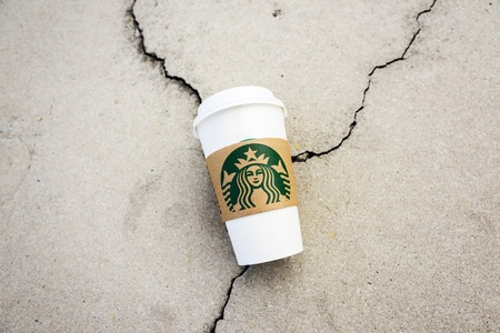 brand damage: BANGKOK, THAILAND - MAY 22, 2015: White paper cup with Starbucks logo on cracking concrete. Starbucks is the worlds largest coffee house with over 20,000 stores in 61 countries. Editorial