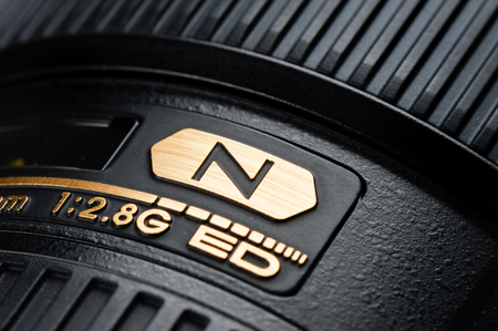 70 s: BANGKOK, THAILAND - MAY 13, 2015: Closeup N logo on name plate of Nikon Lens, lens with Nano Crystal Coat feature. The technology is effective in reducing ghost and flare peculiar to ultra-wideangle lenses.
