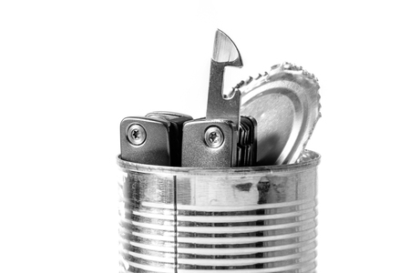 the opener: tin opener and opened tin Stock Photo