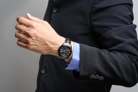 shiny suit: closeup black watch on wrist of businessman