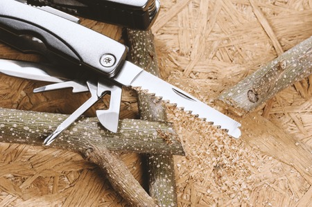 handsaw: using handsaw cutting the branch