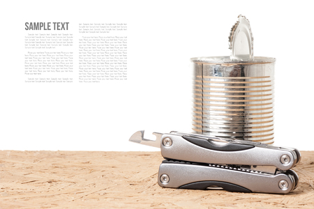 the opener: tin opener and opened tin on wooden desk Stock Photo