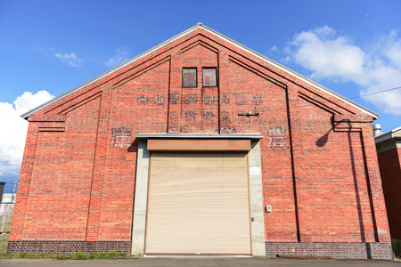 shutter door: facade of old red brick warehouse with shutter door or rolling door Stock Photo