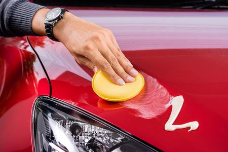 depilacion con cera: cuidado de coche, pulir el coche rojo Foto de archivo
