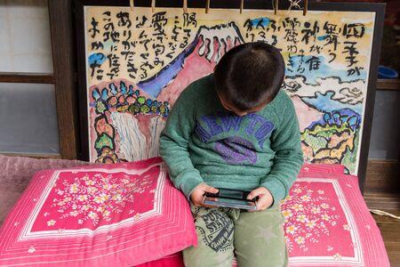 saiko: YAMANASHI, JAPAN - NOVEMBER 04, 2014: Unidentified boy playing handheld game console in Saiko Iyashi no Sato NENBA. Saiko Iyashi no Sato NENBA is a restored traditional village. Editorial