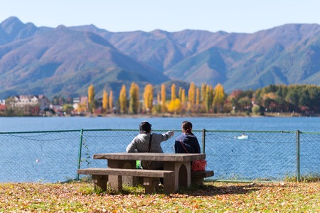fujisan: YAMANASHI, JAPAN - NOVEMBER 03, 2014: Unidentified people sit in front of Lake Kawaguchi, located in Fujikawaguchiko, southern Yamanashi Prefecture near Mount Fuji, Japan.