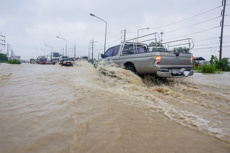 thailand flood: CHONBURI, THAILAND - SEPTEMBER 17, 2015: Many people driving the car through flooded area after the storm VAMCO rain.