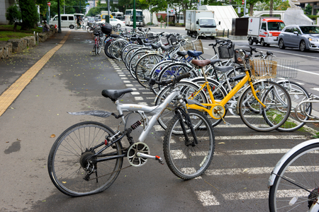 flat tire: HOKKAIDO, JAPAN - JULY 25, 2015: Flat tire bicycle in bicycle parking in Sapporo, Japan. Bicycles are widely used in Japan by people of all age groups and social standings.