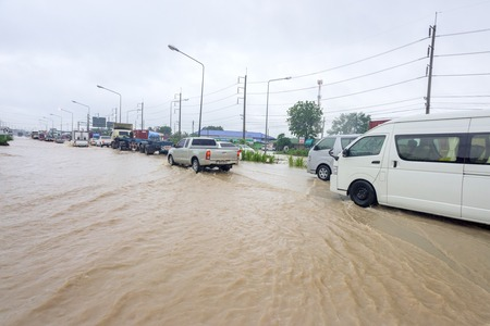 deluge: CHONBURI, THAILAND - SEPTEMBER 17, 2015: Many people driving the car through flooded area after the storm VAMCO rain.