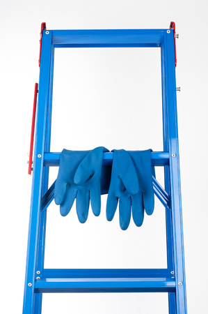 rubber glove: blue rubber glove hanging on ladder Stock Photo