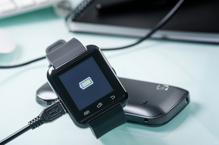 charging battery of black smart watch Foto de archivo